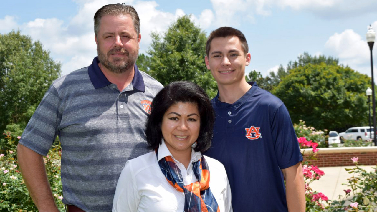 Photo of Food Science doctoral degree alumna Gerri Santos, husband and son, wearing Auburn University clothing, accessories