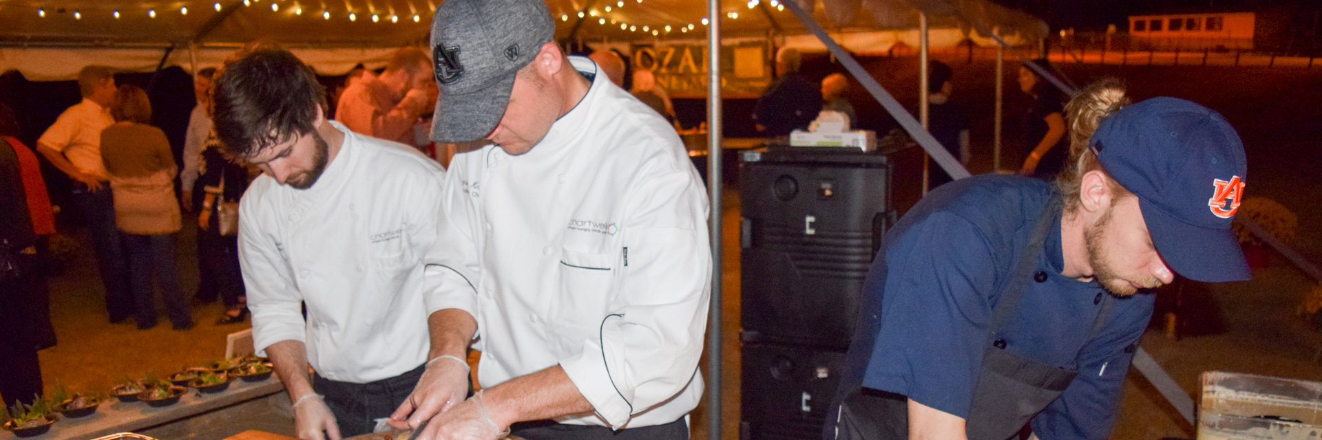 Three chefs, one wearing an Auburn cap, cooking at the Birds n Brews College of Agriculture event