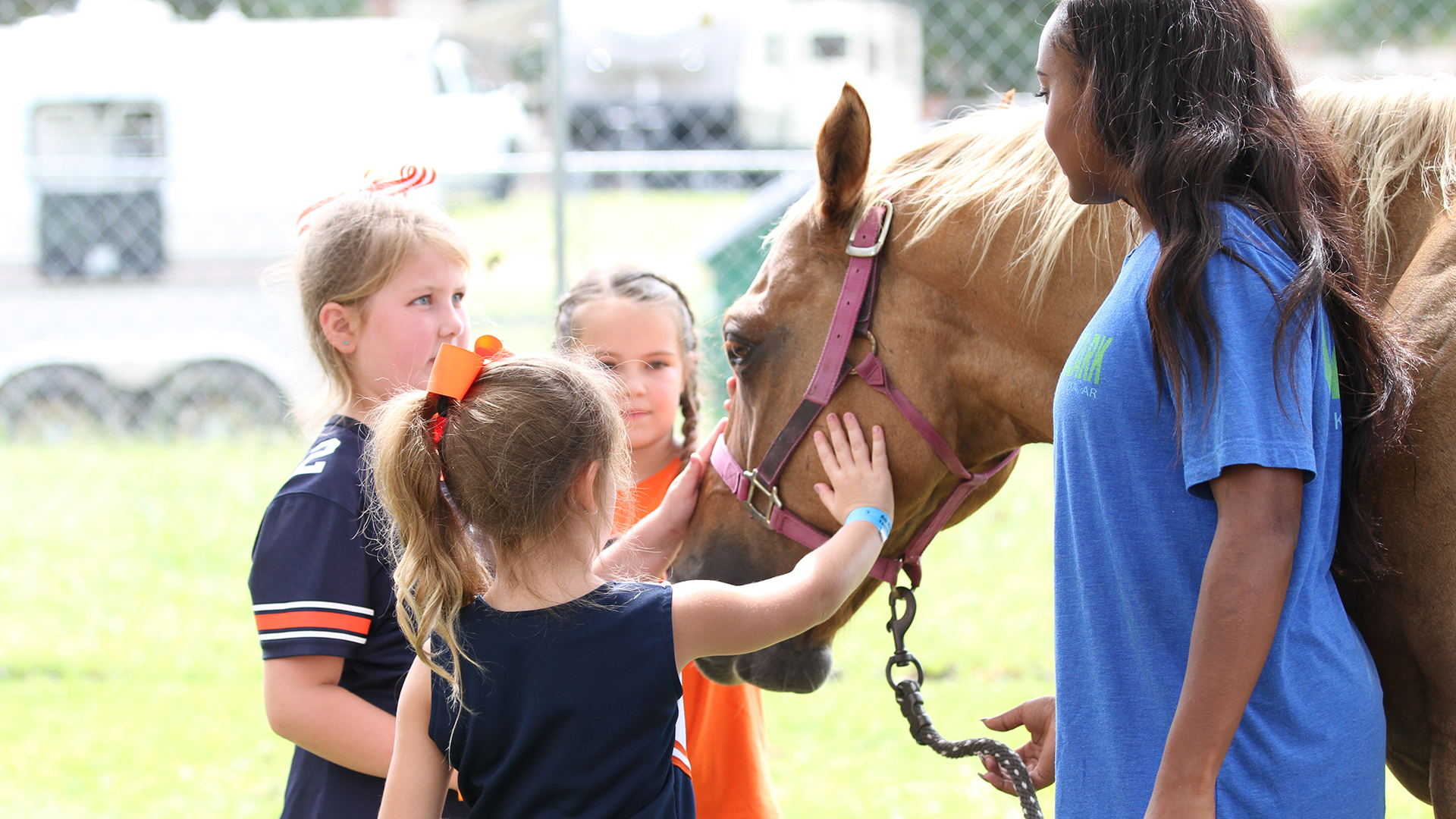 African American female college student, majoring in Animal Sciences, with young girls in Auburn Tigers apparel petting a horse.