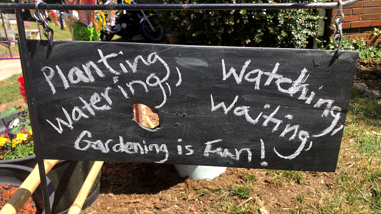 "The owners of a bucket garden near Birmingham proudly display a chalkboard sign reading ""Gardening is fun!"""