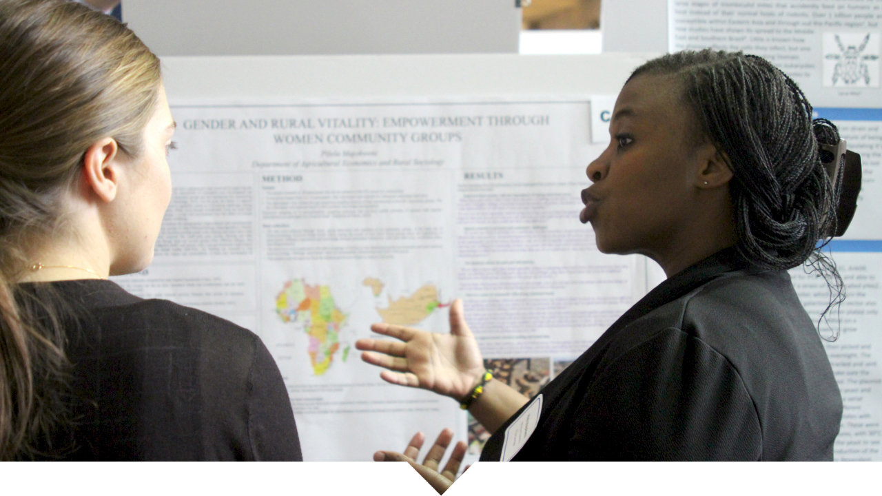Photo of Pilela Majokweni, Agricultural Economics & Rural Sociology grad student presenting her research to another female college student at the Graduate Student Agricultural Poster Showcase.
