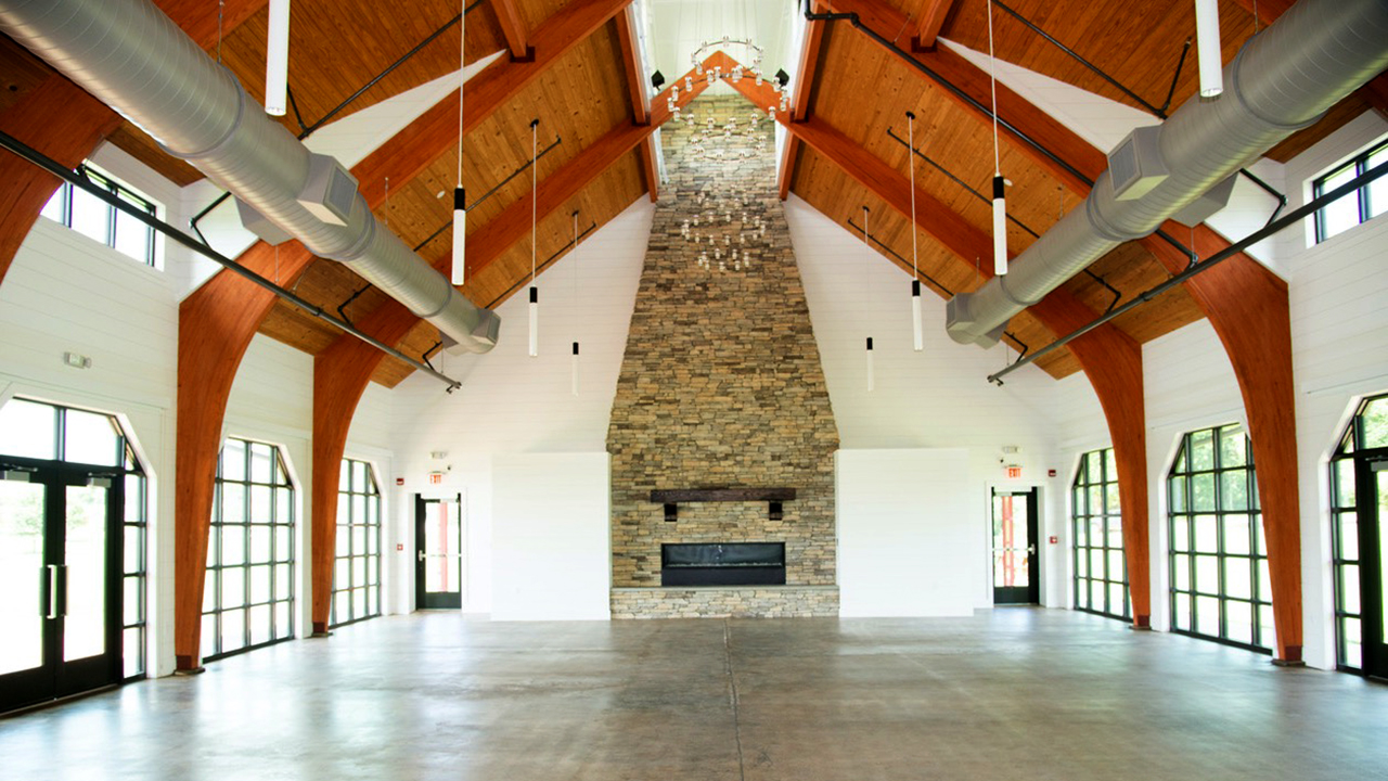 The renovated Ag Heritage Park Pavilion features a large stone fireplace, glass doors and exposed wood ceilings.