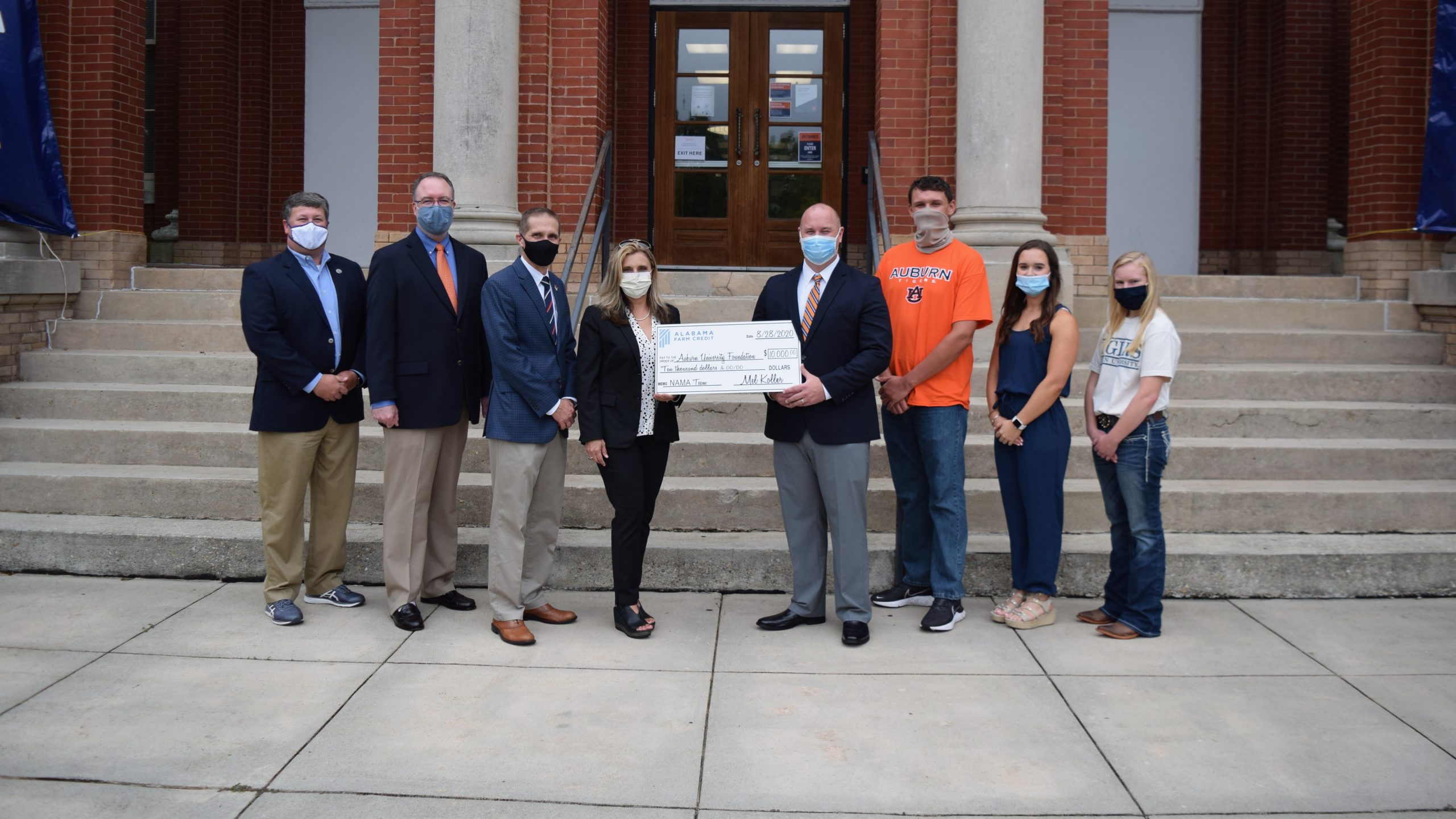 Alabama Farm Credit presents funding check to College of Agriculture, NAMA chapter in front of Auburn University Comer Hall, Alabama, USA