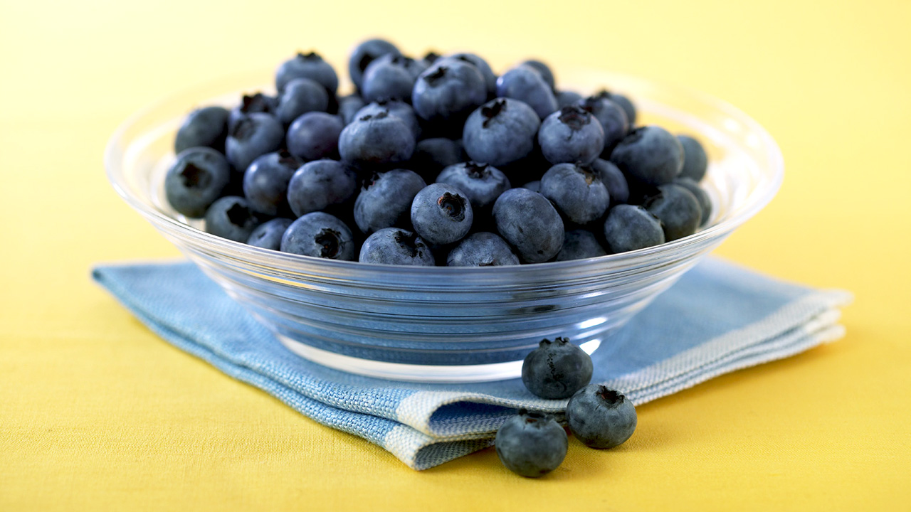 Beautiful glass bowl full of delicious blueberries. Blueberry on yellow table.
