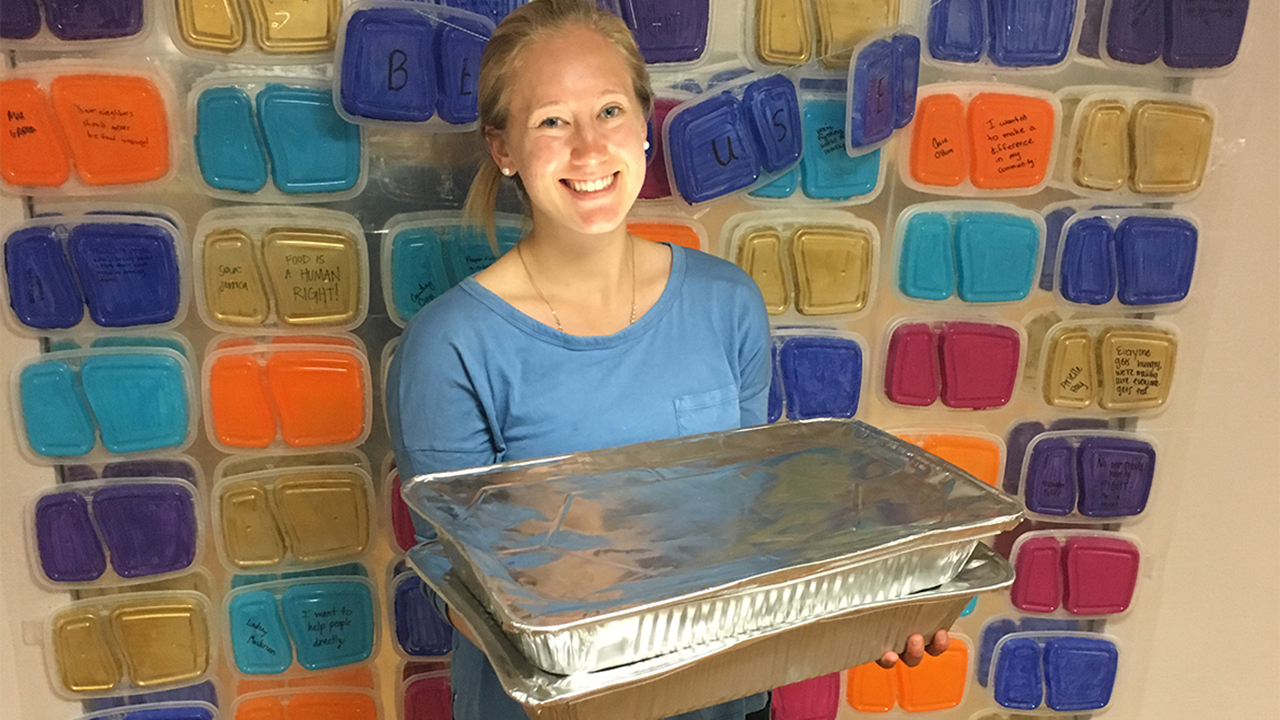 Photo of Kenzley Defler, Auburn graduate holding a tray of food containers behind her