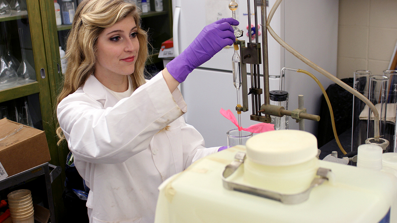 Southern blonde female college undergrad in latex gloves in a research lab coat