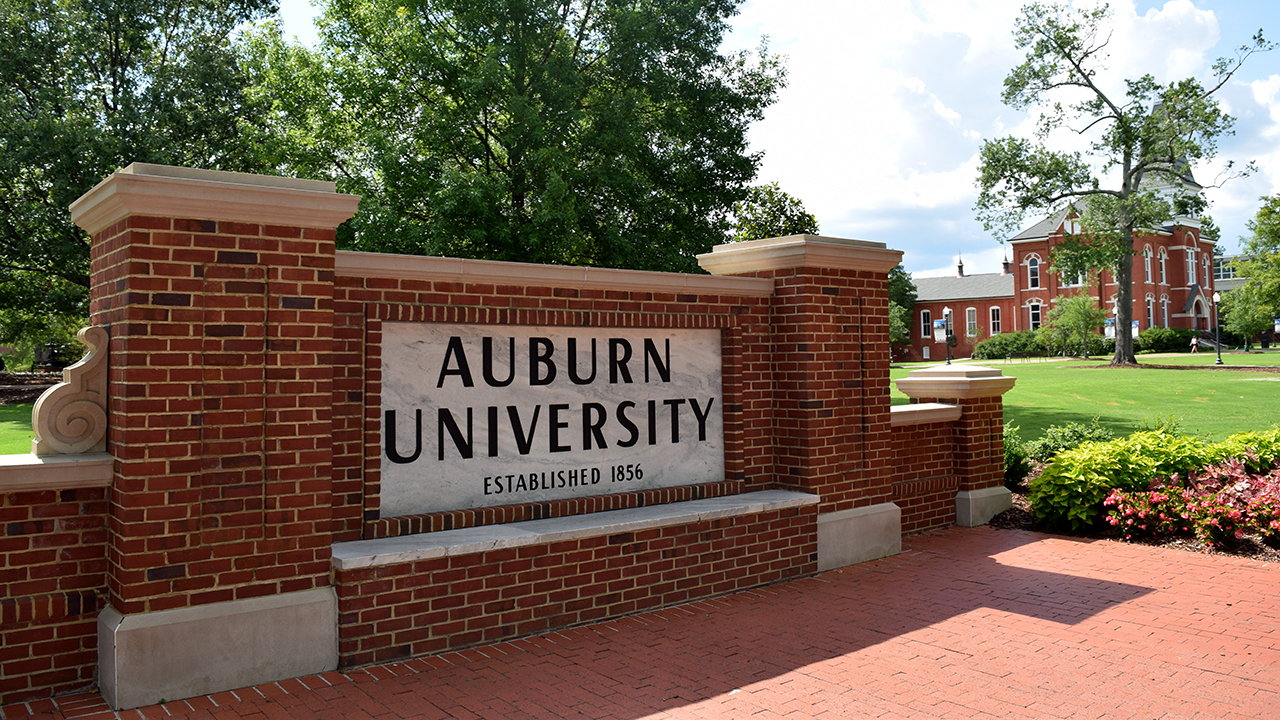 Auburn University, established 1856, main sign on campus that tourists & students take graduation pictures in front of. Sunny summer day.