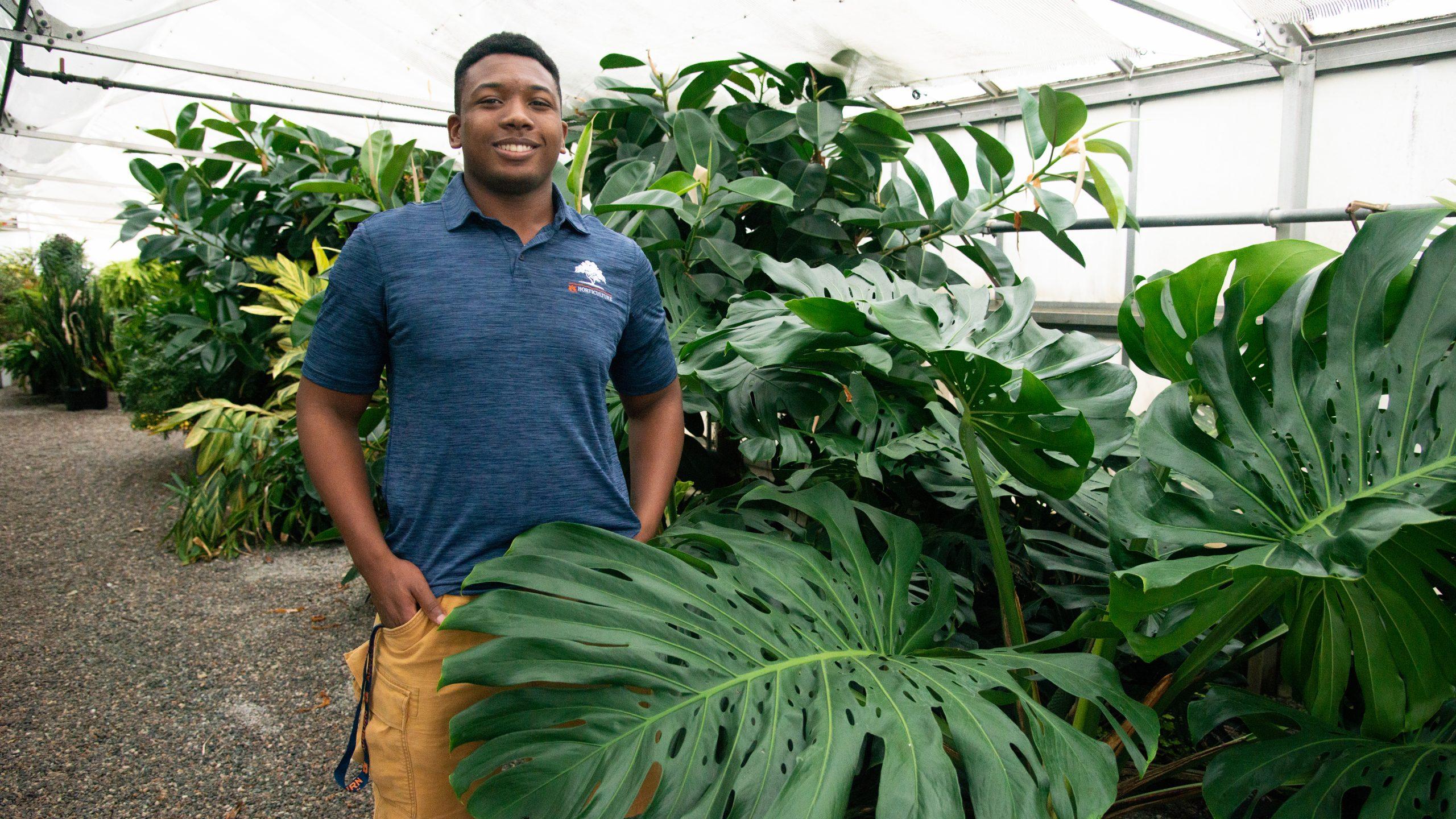 Johnathan Hampton smiles in a greenhouse