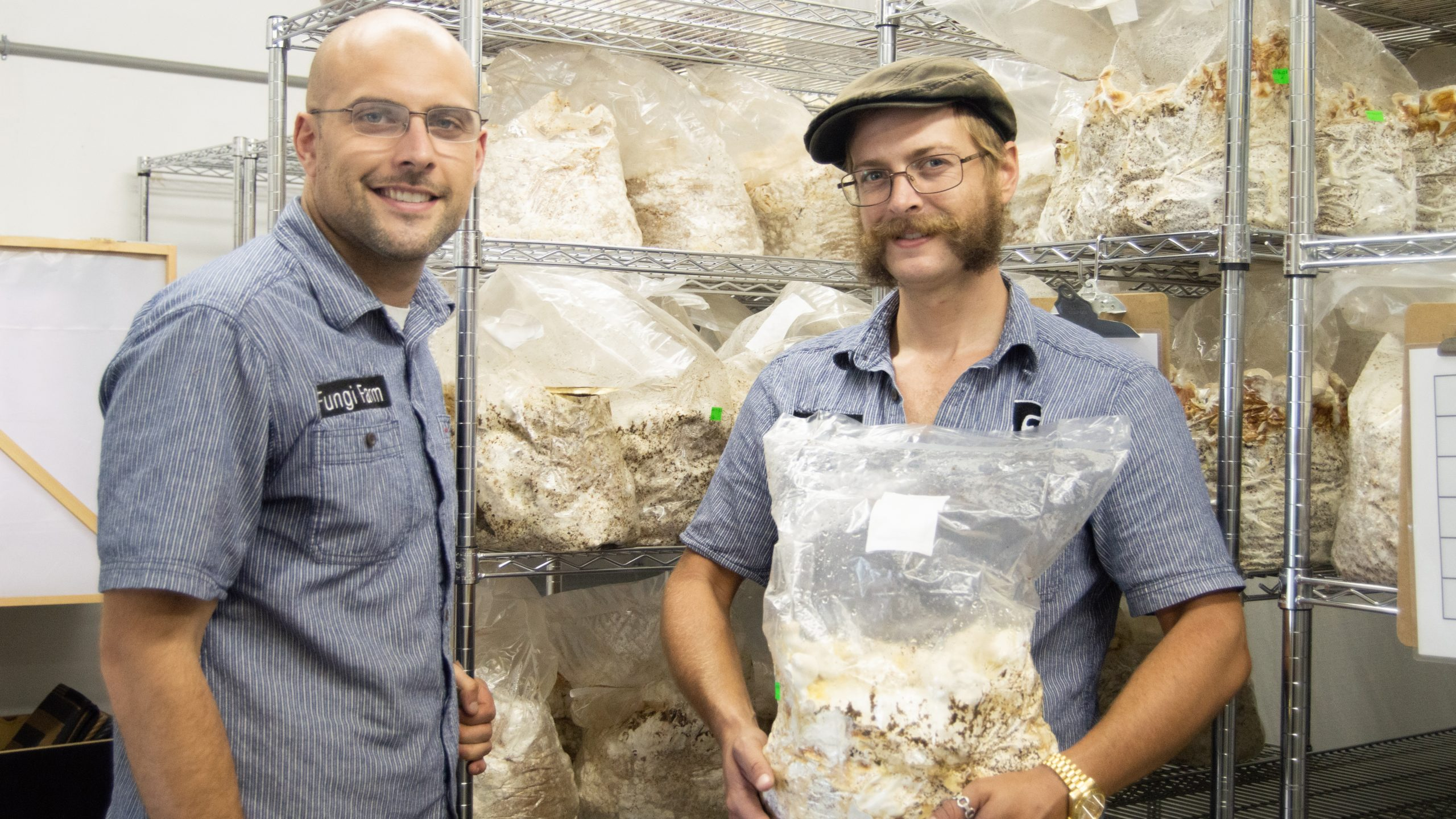 Allen Carroll and Andrew Reynolds in front of bags of mushrooms
