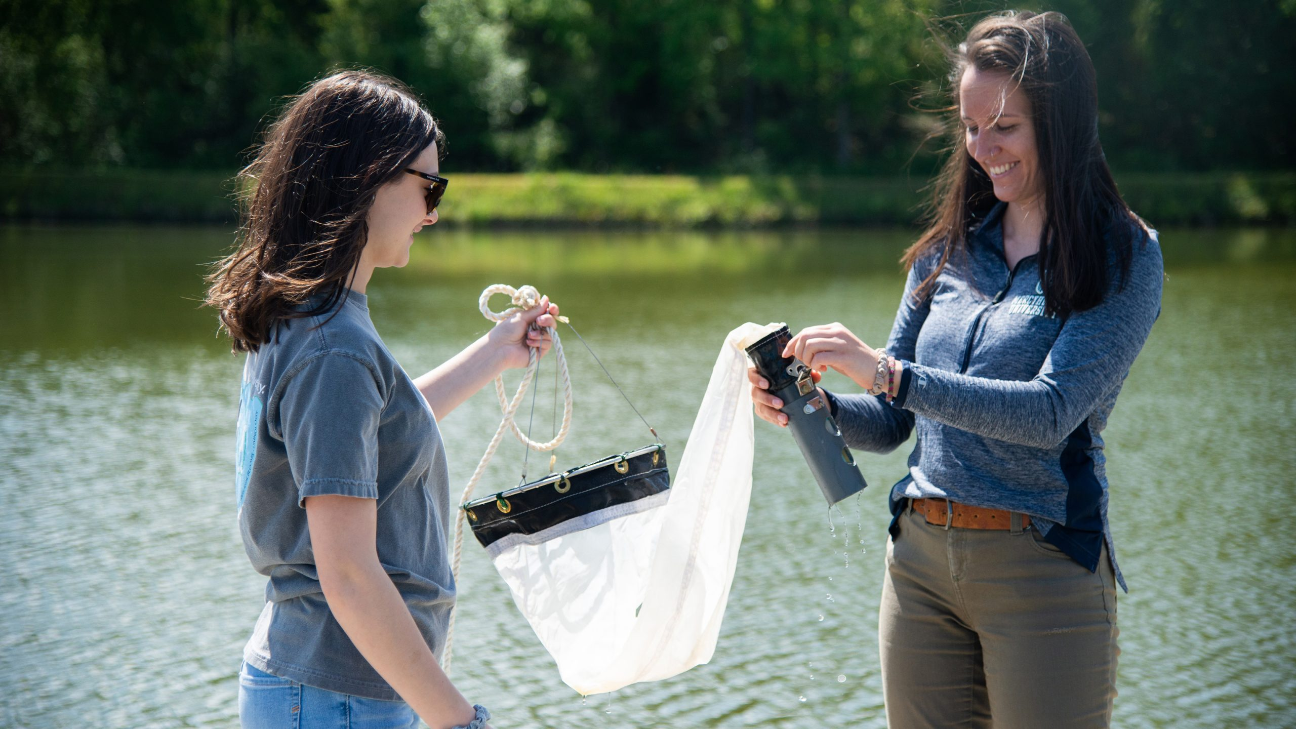 two undergraduate students collect water samples