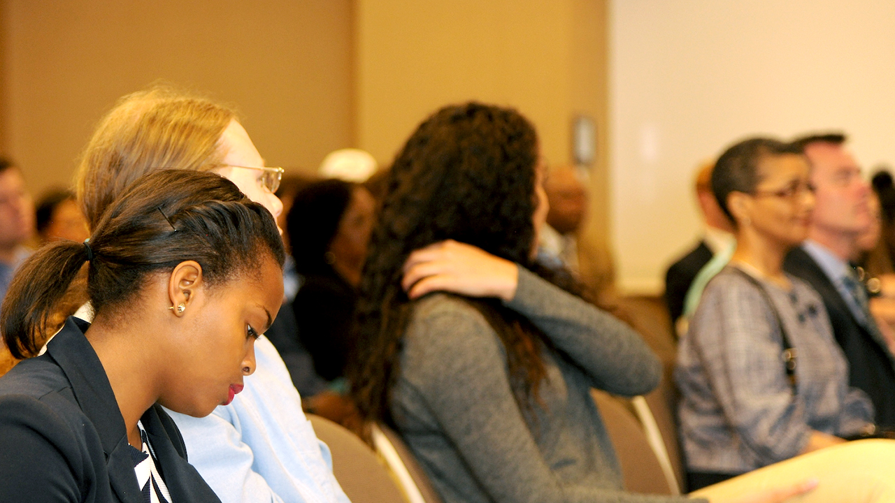 Unity Diversity Event, Attendee hand over shoulder and others listening