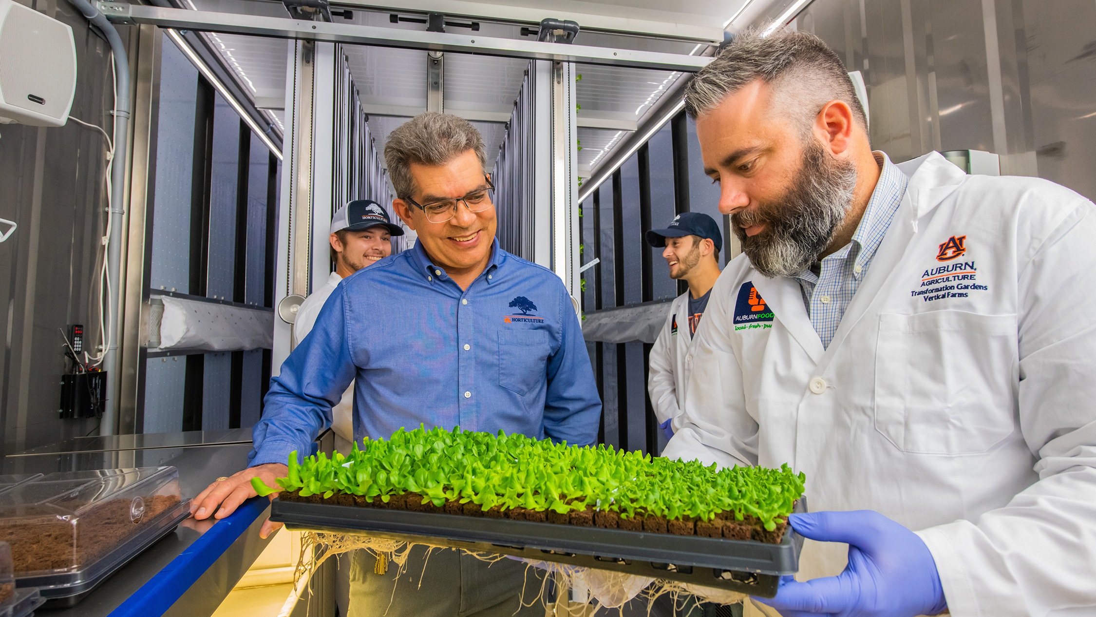 Desmond Layne and Daniel Wells handle plants in a converted shipping container